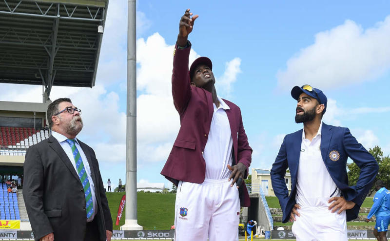 Jason Holder (C) of West Indies tosses the coin as Virat Kohli (R) of India and match referee David Boon (L) look on during day 1 of the 1st Test between West Indies and India at Vivian Richards Cricket Stadium in North Sound, Antigua and Barbuda, on August 22, 2019. (Photo by Randy Brooks / AFP)
