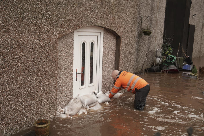 A view of a man piling sandbags outside a house, in Appleby-in-Westmorland, Cumbria, England, Sunday Feb. 9, 2020. Trains, flights and ferries have been cancelled and weather warnings issued across the United Kingdom as a storm with hurricane-force winds up to 80 mph (129 kph) batters the region. (Owen Humphreys/PA via AP)