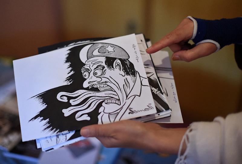 Masouda Khazan Tokhi, a female Afghan satirist, shows cartoons at her home in Kabul (AFP Photo/Wakil Kohsar)