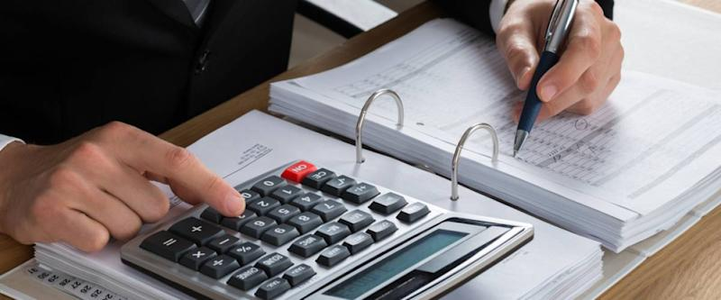 closeup of man's hands doing accounting work on a calculator