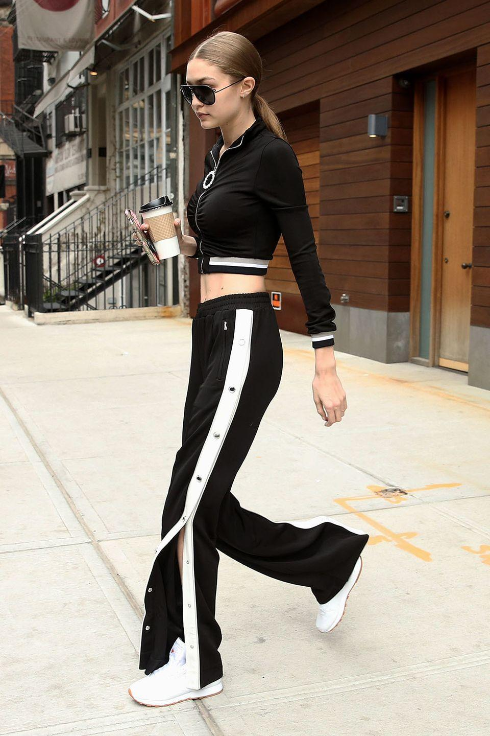 <p>In a cropped black and white track suit by Alessandra Rich, white Reebok sneakers and black Versace aviator sunglasses while leaving her apartment in NYC.</p>