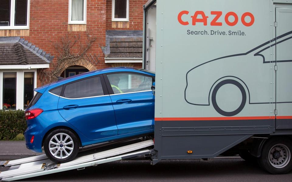 A Cazoo employee reverses a second hand automobile out of a transportation vehicle outside a residential property in Southampton - Chris Ratcliffe/Bloomberg