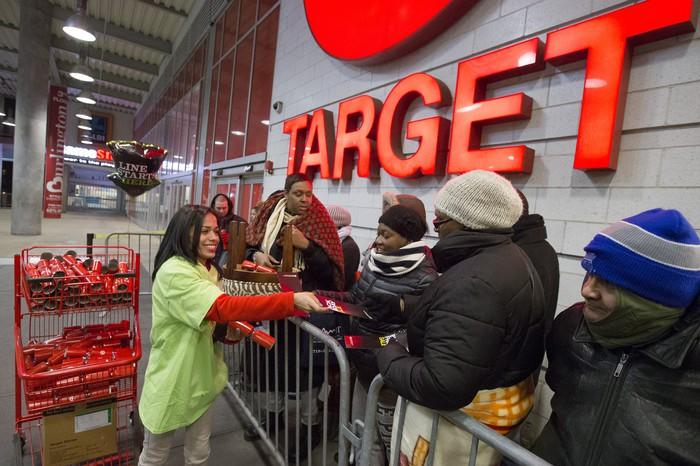 Target employee hands out flyer to shoppers