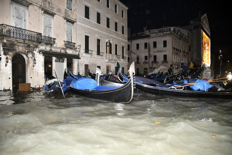 FILE - In this Wednesday, Nov. 13, 2019 file photo, stranded gondolas float adrift over the flooded banks, in Venice, Italy. Venice's hoteliers association estimates that the city's hotels suffered about 30 million euros ($34 million) worth of structural damage during November's floods. The overall losses though are higher when the lower revenues that local hotels have reported in the wake of the surging high tides are added in. (AP Photo/Luigi Costantini, File)