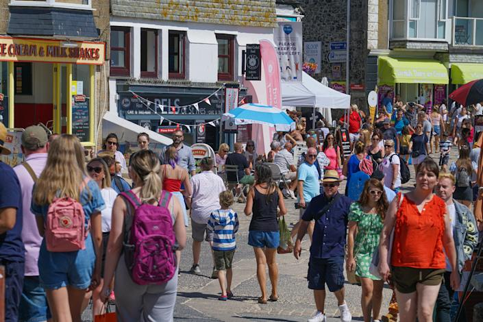 Holiday-makers walk the narrow streets in St Ives, Cornwall, during the heatwave. (Getty)