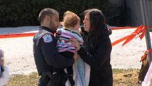 A Gatineau police officer hands over a child to her mother after the April 5 daycare shooting that left two men dead.