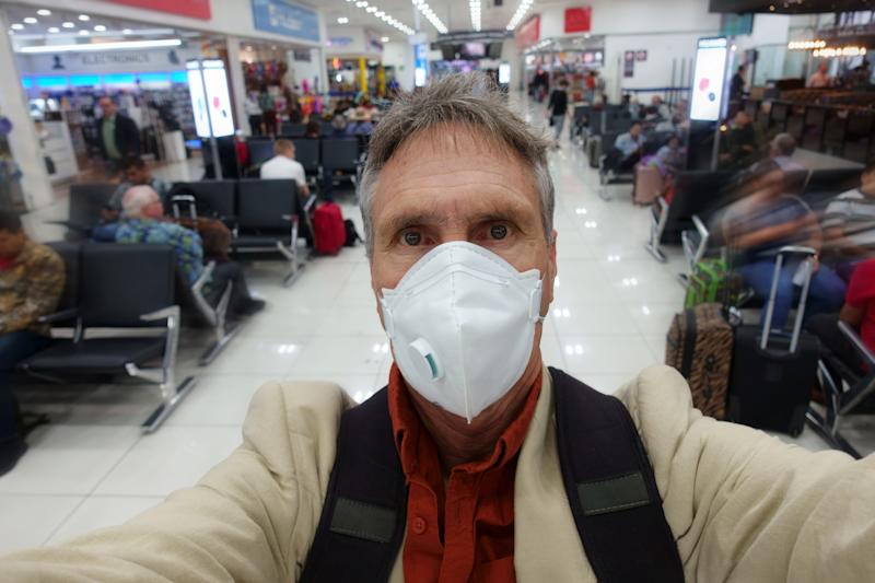 Man taking a selfie while wearing protective face mask in airport.