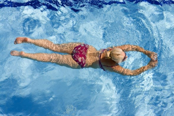 Active mature woman swimming in the pool.