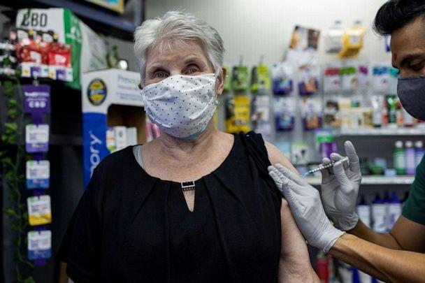 PHOTO: A woman receives the Pfizer-BioNTech coronavirus disease (COVID-19) vaccine as a booster dose at Skippack Pharmacy in Schwenksville, Pennsylvania, Aug. 14, 2021. (Hannah Beier/Reuters, FILE)