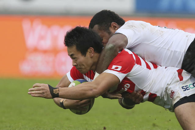 FILE - In this Nov. 26, 2016, file photo, Kenki Fukuoka, bottom, of Japan is tackled by Nikola Matawalu of Fiji during the international rugby union test match between Fiji and Japan at Stade de la Rabine in Vannes, western France. Japan speedster Fukuoka reportedly will forego the chance to compete in rugby sevens at the postponed Tokyo Olympics in order to pursue a medical career. The Japan Rugby Union announced that Fukuoka had left the national sevens squad. (AP Photo/David Vincent, File)