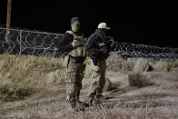 """Police officers guard an entrance to the Nevada Test and Training Range near Area 51 Friday, Sept. 20, 2019, near Rachel, Nev. People gathered at the gate inspired by the """"Storm Area 51"""" internet hoax. (AP Photo/John Locher)"""