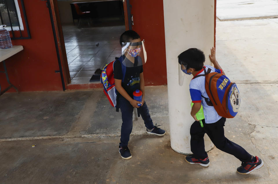 Wearing masks and face shields to curb the spread of the new coronavirus, two students play during the first day of class at the Valentin Gomez Farias Indigenous Primary School in Montebello, Hecelchakan, Campeche state, Monday, April 19, 2021. Campeche is the first state to transition back to the classroom after a year of remote learning due to the pandemic. (AP Photo/Martin Zetina)