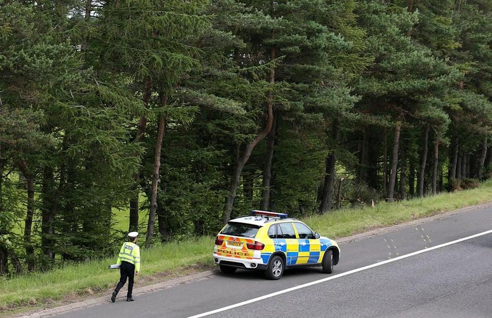 A police officer searching the scene at Junction 9 of the M9 near Stirling where John Yuill and Lamara Bell were discovered (Andrew Milligan/PA) (PA Wire)