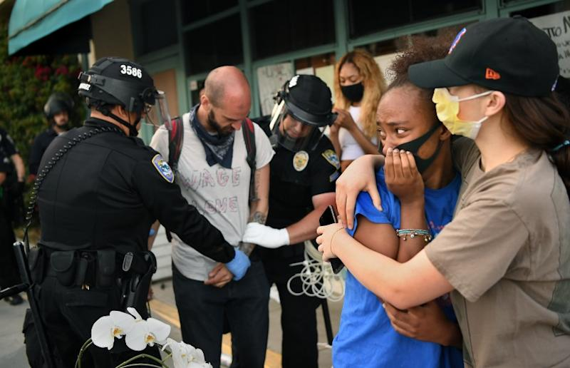 SANTA MONICA, CALIFORNIA MAY 31, 2020-Protestors embrace as another is led away in handcuffs on 5th St. in Santa Maonica Sunday. (Wally Skalij/Los Angeles Times)