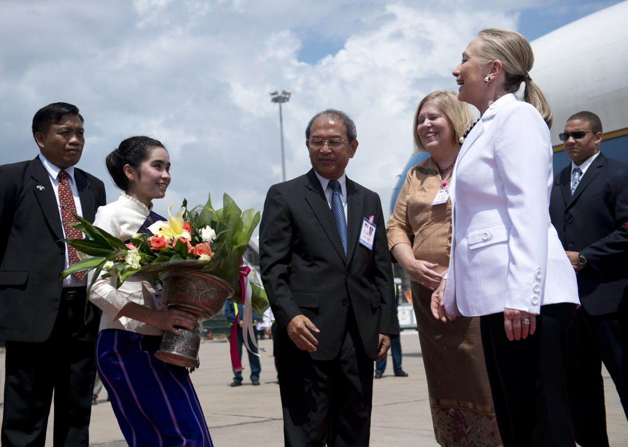 U.S. Secretary of State Hillary Rodham Clinton, right, arrives at Wattay International Airport in Vientiane, Laos, Wednesday, July 11, 2012. (AP Photo/Brendon Smialowski, Pool)