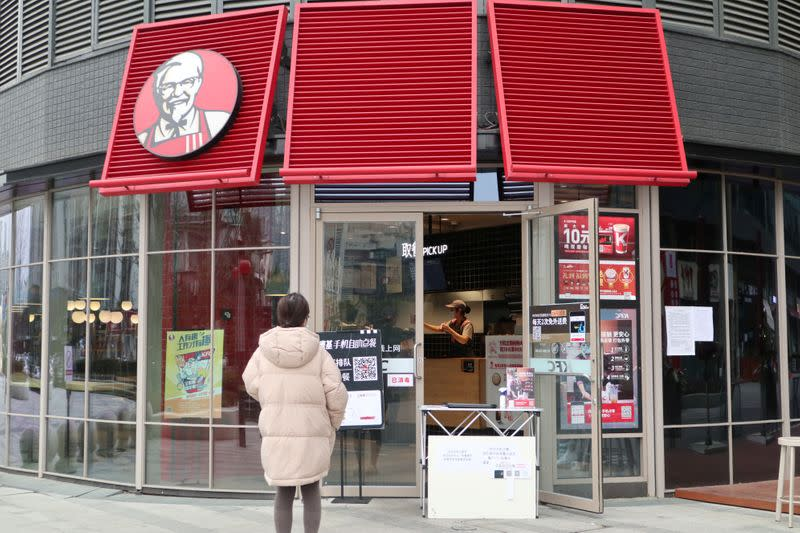 FILE PHOTO: Customer waits to pick up her order outside a KFC restaurant as the country is hit by an outbreak of the novel coronavirus, in Chengdu