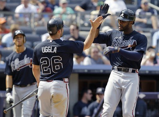 Atlanta Braves' Dan Uggla (26) greets Jason Heyward at the plate after Uggla scored on Heyward's eighth-inning, two-run home run during a baseball game at Yankee Stadium in New York, Wednesday, June 20, 2012. On-deck batter Andrelton Simmons is at left rear. (AP Photo/Kathy Willens)
