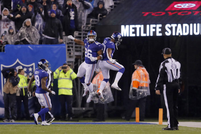 New York Giants running back Saquon Barkley (26) celebrates a touchdown with Giants running back Javorius Allen (37) in the second half of an NFL football game against the Philadelphia Eagles, Sunday, Dec. 29, 2019, in East Rutherford, N.J. (AP Photo/Adam Hunger)