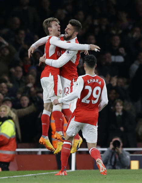 Arsenal's Nacho Monreal, left celebrates with teammates after he scored the opening goal of the game during the English Premier League soccer match between Arsenal and Leicester City at the Emirates Stadium in London, Wednesday, April 26, 2017. (AP Photo/Alastair Grant)