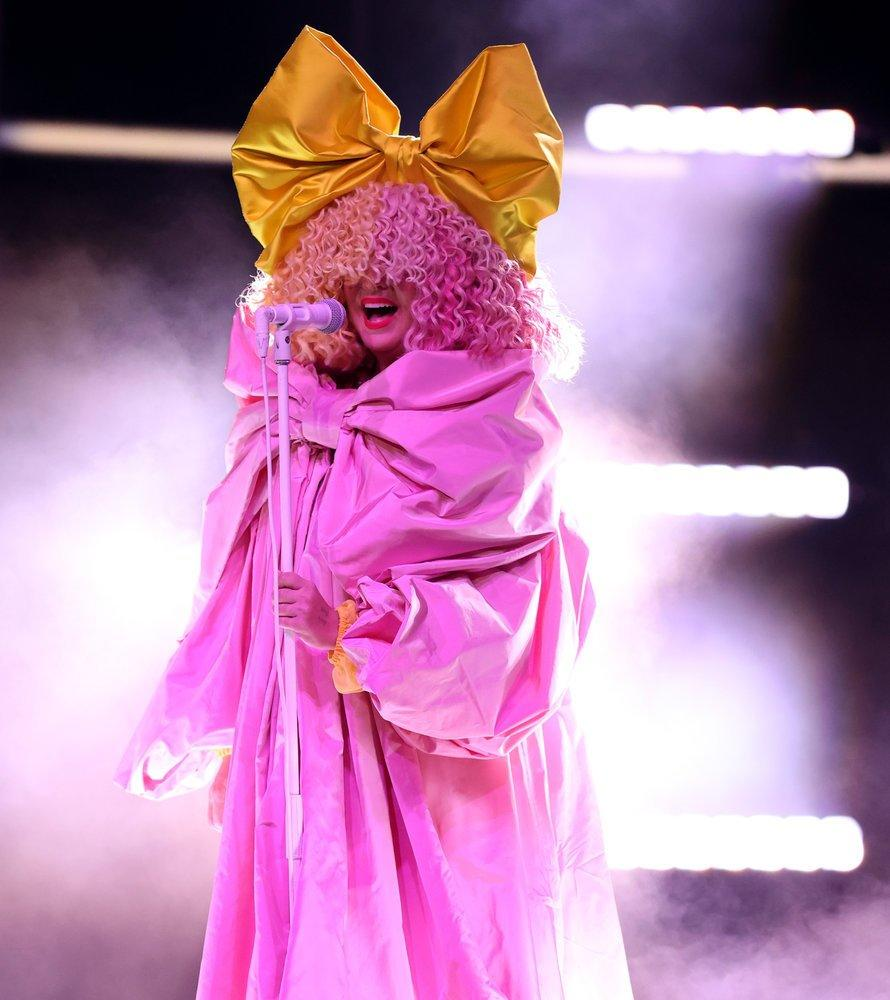 Sia wears a billowing pink gown, blond and pink curly wig that covers the top half of her face, and a gold bow.