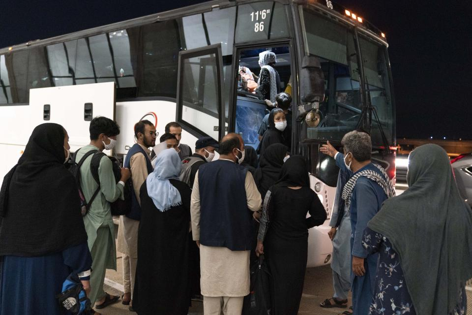 Families evacuated from Kabul, Afghanistan, are loaded into a buses after they arrived at Washington Dulles International Airport, in Chantilly, Va., on Saturday, Aug. 21, 2021. (Jose Luis Magana/AP)