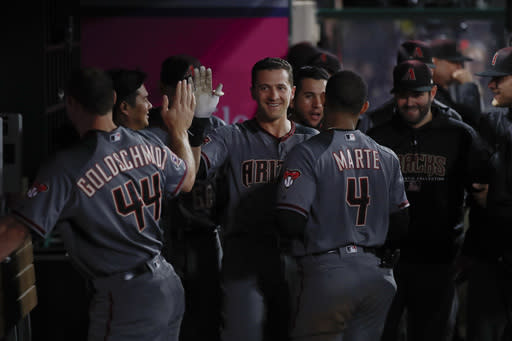 Arizona Diamondbacks' Nick Ahmed, center, is greeted by teammates in the dugout after hitting a home run during the eighth inning of a baseball game against the Los Angeles Angels, Monday, June 18, 2018, in Anaheim, Calif. (AP Photo/Jae C. Hong)