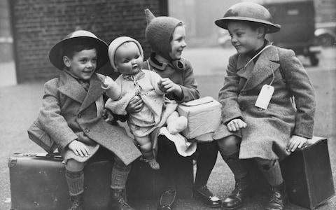 26th October 1940: Three young evacuees sit on their suitcases ready for their journey away from the danger of the city - Credit: Reg Speller/Fox Photos/Getty Images