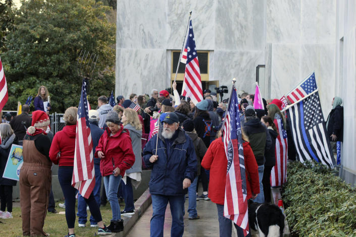 FILE - In this Dec. 21, 2020, file photo, pro-Trump and anti-mask demonstrators hold a rally outside the Oregon State Capitol as legislators meet for an emergency session in Salem, Ore. During the protest Republican lawmaker, Rep. Mike Nearman, physically opened the Capitol's door — letting protesters, who clashed with police, gain access to the building. There have been calls for Nearman to resign ahead of the upcoming 2021 Legislative session that begins Tuesday, Jan. 19, 2021. (AP Photo/Andrew Selsky, File)