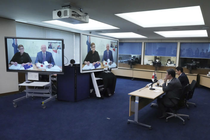 Japanese Foreign Minister Toshimitsu Motegi, second right, and Defense Minister Nobuo Kishi, right, attend a video conference with Australian Foreign Minister Marise Payne, left on screen, and Australian Defense Minister Peter Dutton, right on screen, at Foreign Ministry in Tokyo during their two-plus-two ministerial meeting Wednesday, June 9, 2021, in Tokyo. (AP Photo/Eugene Hoshiko, Pool)