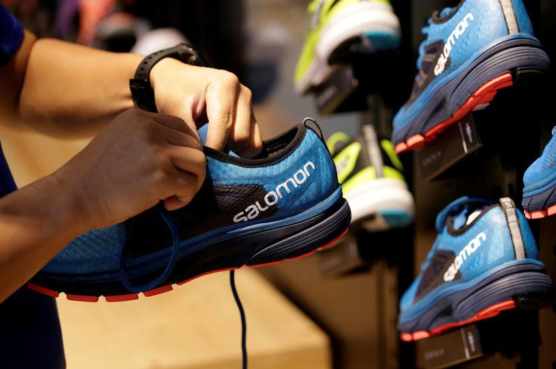 FILE PHOTO: A shop assistant holds a shoe at a Salomon store in Beijing