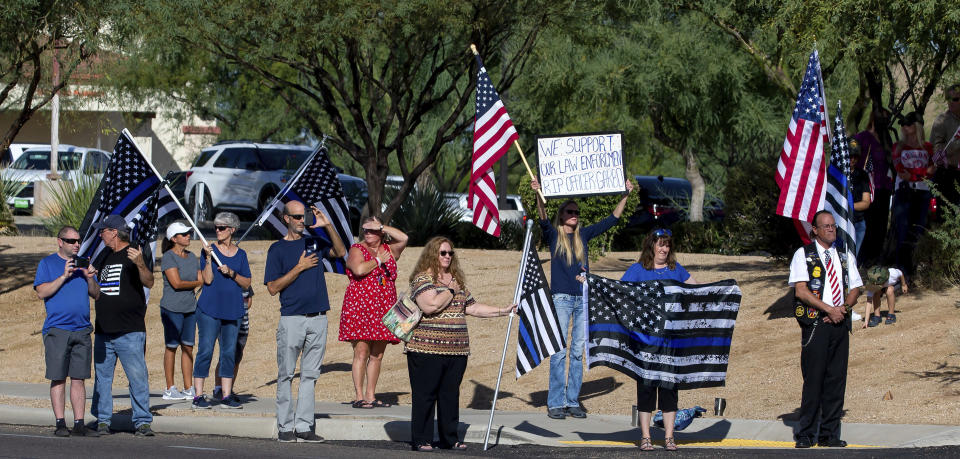 People stand outside Calvary Chapel as the funeral procession for Drug Enforcement Administration Supervisory Special Agent Michael G. Garbo enters the parking lot of Calvary Chapel in Tucson, Ariz. on Friday, Oct. 8, 2021. Garbo, a federal agent shot and killed while questioning a passenger on an Amtrak train in Arizona, was remembered Friday as a venerated leader and mentor with an unparalleled work ethic. (Rebecca Sasnett/Arizona Daily Star via AP)