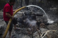 A man extinguishes a fire in Akcayaka village in Milas area of the Mugla province, Turkey, Friday Aug. 6, 2021. Thousands of people fled wildfires burning out of control in Greece and Turkey on Friday, as a protracted heat wave turned forests into tinderboxes that threatened populated areas, electricity installations and historic sites. (AP Photo/Emre Tazegul)