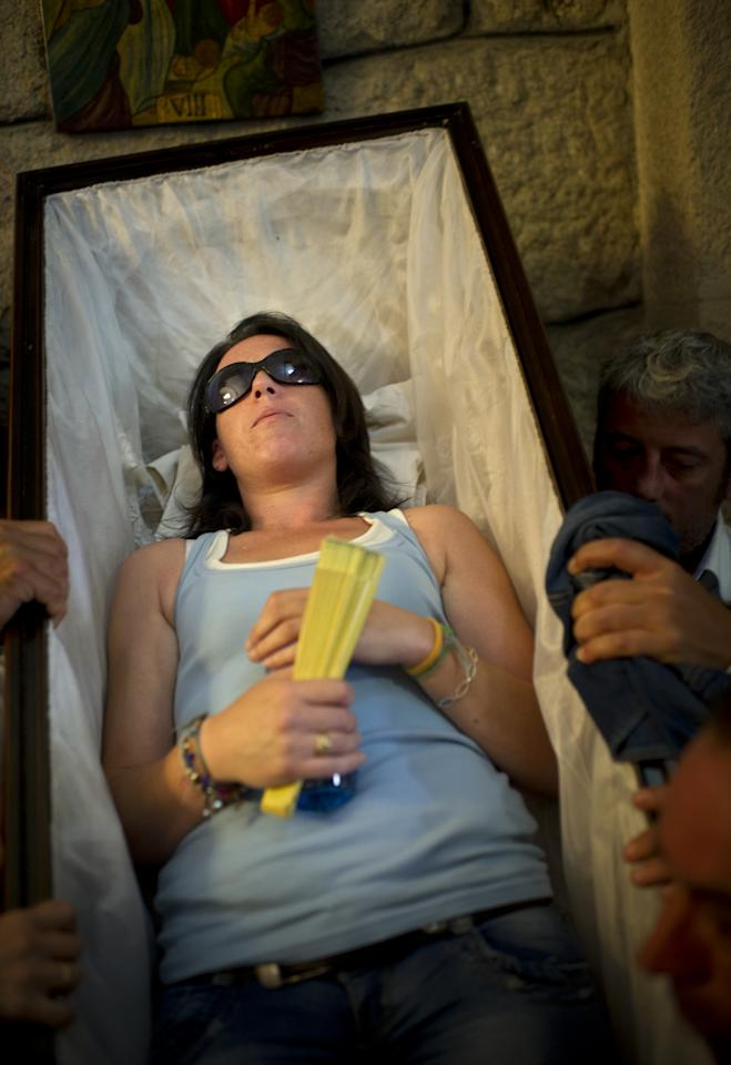 SANTA MARTA DE RIBARTEME, SPAIN - JULY 29: Emilia is lifted up in a coffin to take part in a procession keeping a promise made for her father Jose Manuel, aged 76, after he survived a heavy operation, after a mass on July 29, 2012 in Santa Marta de Ribarteme, Spain. Every year, in the small village of Santa Marta de Ribarteme, which is part of the Las Nieves municipaltie, one of the most curious pilgrimages in Spain is held. Starting after a mass at the village's parish church, believers grateful for the miracle of being saved from death go on a pilgrimage in a procession of coffins. Carried by friends and relatives and while 'Virgin Santa Martha, star of the North, we bring you those who saw death' is song out loud, the pilgrim's process from the cemetery back to the church to round it together with the parish church statue of Saint Marta de Ribarteme, the patron Saint of resurrection.  (Photo by Jasper Juinen/Getty Images)