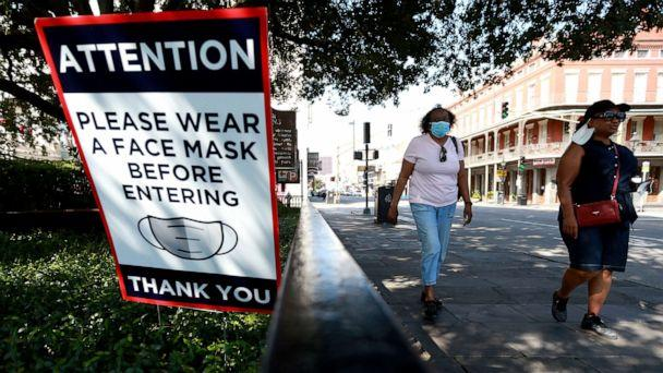 PHOTO: Visitors walk past face mask signs along Decatur Street in the French Quarter on July 14, 2020 in New Orleans, Louisiana. (Sean Gardner/Getty Images)