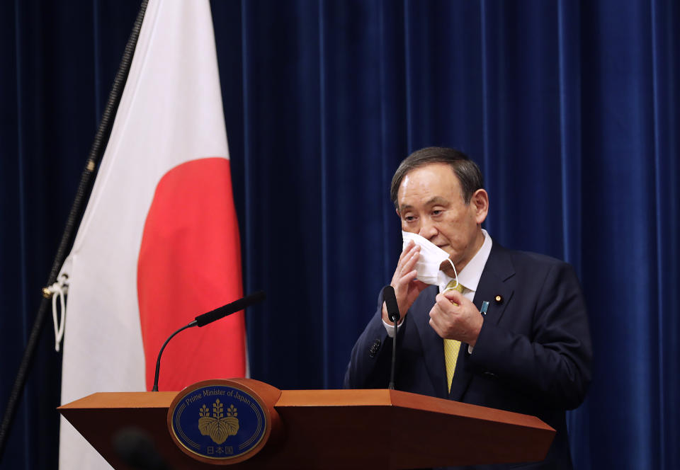 Japanese Prime Minister Yoshihide Suga removes his face mask during a news conference in Tokyo on Friday, Dec. 4, 2020. Suga announced a 2 trillion green fund to promote innovation and technology to achieve his pledge to achieve a carbon free society by 2050.(AP Photo/Hiro Komae, Pool)