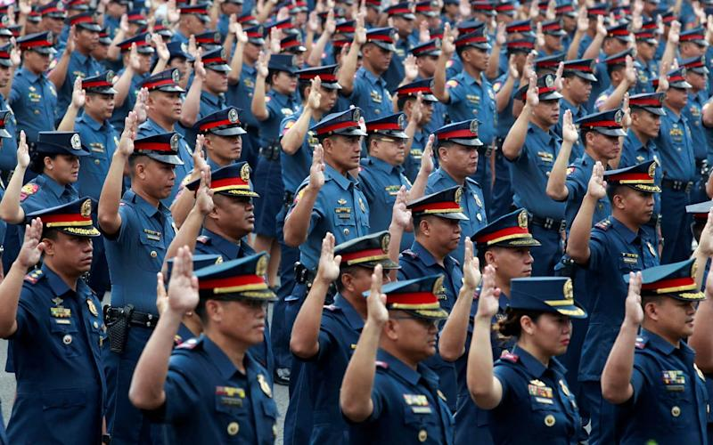 Police officers take their oath at the Philippine National Police (PNP) headquarters in Manila, Philippines. - Credit: Reuters