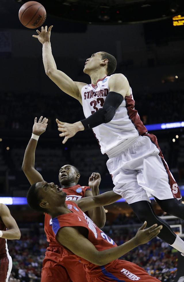 Dayton forward Dyshawn Pierre (21) falls to the court as Stanford forward Dwight Powell (33) shoots during the second half in a regional semifinal game at the NCAA college basketball tournament, Thursday, March 27, 2014, in Memphis, Tenn. (AP Photo/Mark Humphrey)