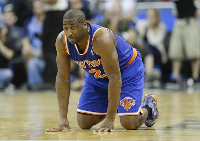 New York Knicks' Raymond Felton kneels on the court after he was injured in the second half of an NBA basketball game against the Orlando Magic in Orlando, Fla., Monday, Dec. 23, 2013. Felton left the game and did not return but New York won 103-98.(AP Photo/John Raoux)