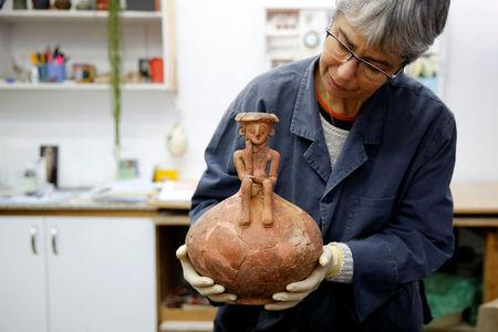 Conservationist Elisheva Kamaisky, shows journalists a 3,800 year-old pottery jug with a rare statuette, discovered during excavation in central Israel, at the Israel Antiquities Authority offices in Jerusalem November 23, 2016. REUTERS/Ammar Awad