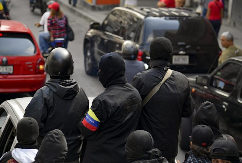 Masked members of a pro-government colectivo cell attend a rally in Caracas on January 7, 2019 (AFP Photo/YURI CORTEZ)