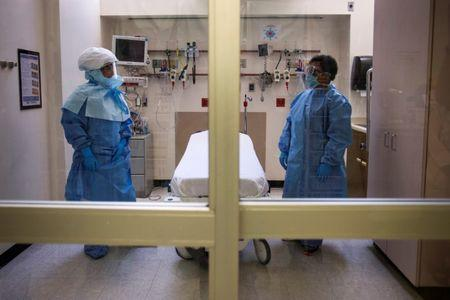 FILE PHOTO: Health care workers display protective gear, which hospital staff would wear to protect them from Ebola infection, inside an isolation room as part of a media tour in the emergency department of Bellevue Hospital in Manhattan, New York October 8, 2014.  REUTERS/Adrees Latif