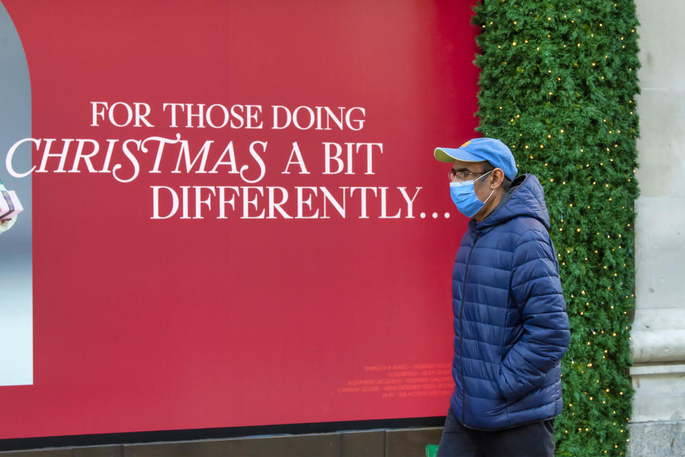 "A man walks past a Christmas poster with the words ""For those doing Christmas a bit different"" outside the Selfridges store in London's Oxford Street on the eve of the second lockdown in London. (Photo by Dave Rushen / SOPA Images/Sipa USA)"