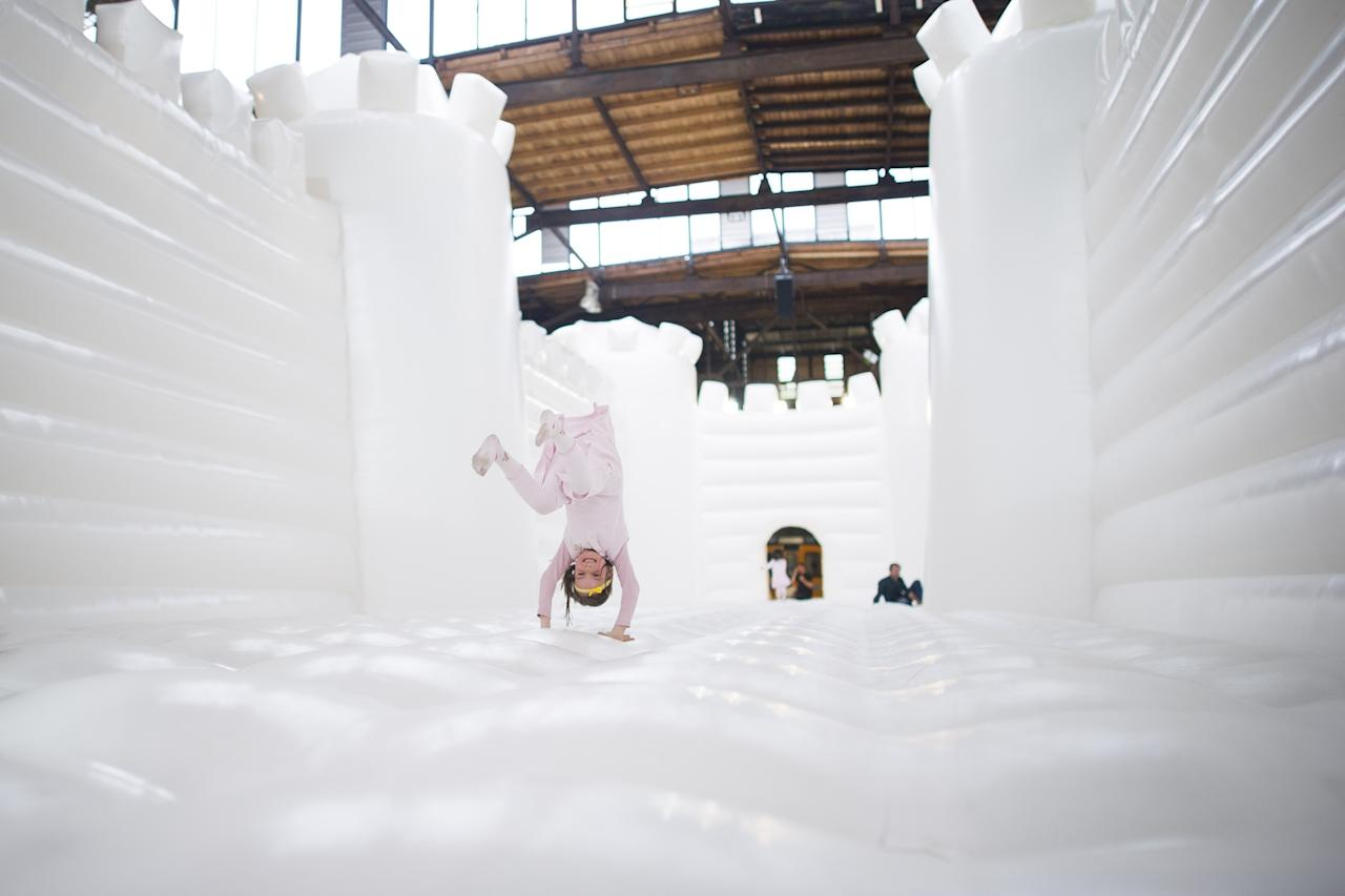 "BERLIN, GERMANY - JUNE 27: A child jump in the ""White Bouncy Castle"" of installation artist William Forsythe on June 27, 2013 in Berlin, Germany. The work is a giant, inflatable white castle that Forsythe says encourages people to dance the moment they step into it. ""White Bouncy Castle"" will be open to visitors at Lokhalle Schoeneberg until July 14 and is part of the ""Foreign Affairs"" series of Berliner Festspiele. (Photo by Timur Emek/Getty Images)"