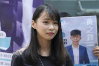 In this Saturday, Sept. 28, 2019, photo, Hong Kong pro-democracy activist Agnes Chow, stands next to an election campaign poster of pro-democracy activist Joshua Wong, in Hong Kong. Chow and activist Ivan Lam have been sentenced to jail on Wednesday, over charges related to an unauthorized anti-government protest last year at the city's police headquarters. (AP Photo/Kin Cheung)