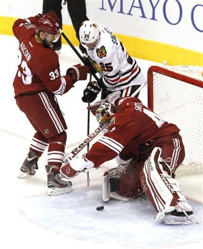 Phoenix Coyotes' Mike Smith, right, makes a save on a shot by Chicago Blackhawks' Viktor Stalberg (25), of Sweden, as Coyotes' Adrian Aucoin (33) defends during the first period in Game 5 of an NHL hockey Stanley Cup first-round playoff series Saturday, April 21, 2012, in Glendale, Ariz.AP Photo/Ross D. Franklin)