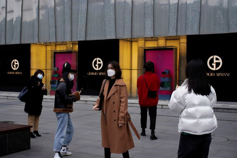 People wearing face masks are seen outside a Giorgio Armani store at a shopping mall in Wuhan