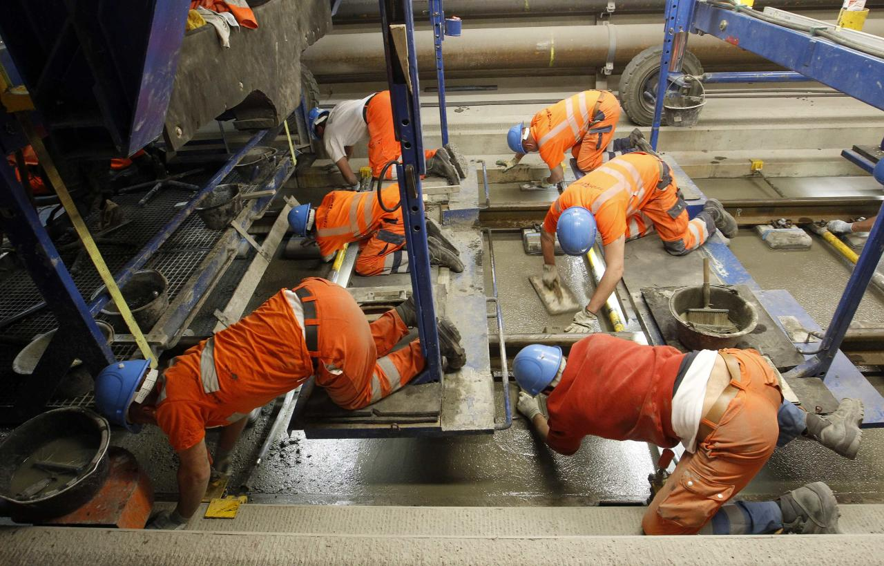 Workers use finishing trowels to plane fresh concrete on the track bed of the rails in the NEAT Gotthard Base tunnel near Erstfeld May 7, 2012. Crossing the Alps, the world's longest train tunnel should become operational at the end of 2016. The project consists of two parallel single track tunnels, each of a length of 57 km (35 miles) REUTERS/Arnd Wiegmann   (SWITZERLAND - Tags: BUSINESS CONSTRUCTION EMPLOYMENT TRAVEL)