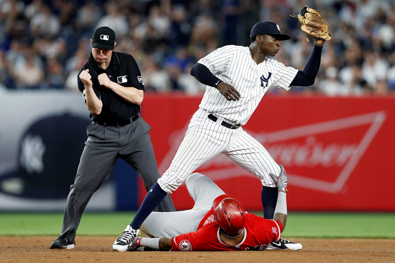 May 25, 2018; Bronx, NY, USA; Los Angeles Angels catcher Martin Maldonado (12) is tagged out by New York Yankees shortstop Didi Gregorius (18) in front of second base umpire Mike Estabrook (83) during the seventh inning at Yankee Stadium. Mandatory Credit: Adam Hunger-USA TODAY Sports     TPX IMAGES OF THE DAY