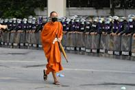 A Buddhist monk walks past riot police standing guard during an anti-government rally by pro-democracy protesters in Bangkok on November 17, 2020.