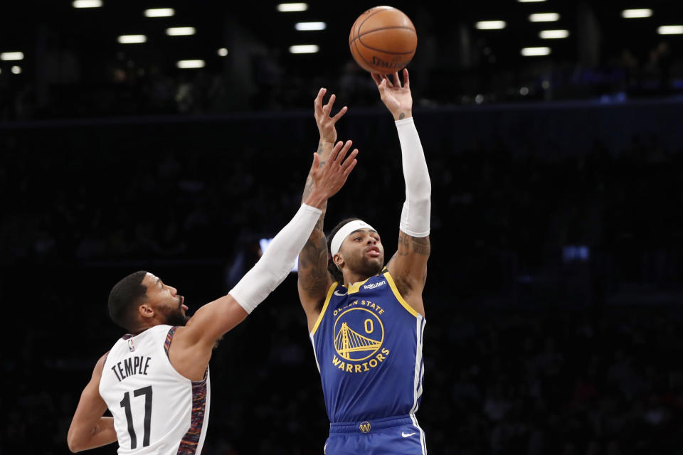 Golden State Warriors guard D'Angelo Russell (0) shoots next to Brooklyn Nets guard Garrett Temple (17) during the first half of an NBA basketball game Wednesday, Feb. 5, 2020, in New York. (AP Photo/Kathy Willens)